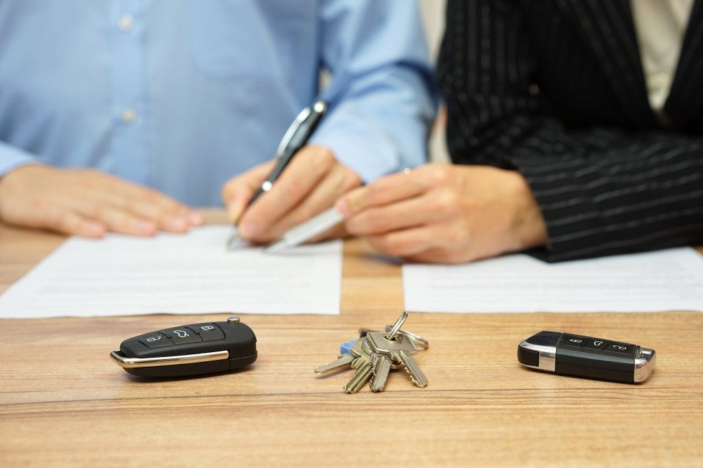 two people signing auto papers
