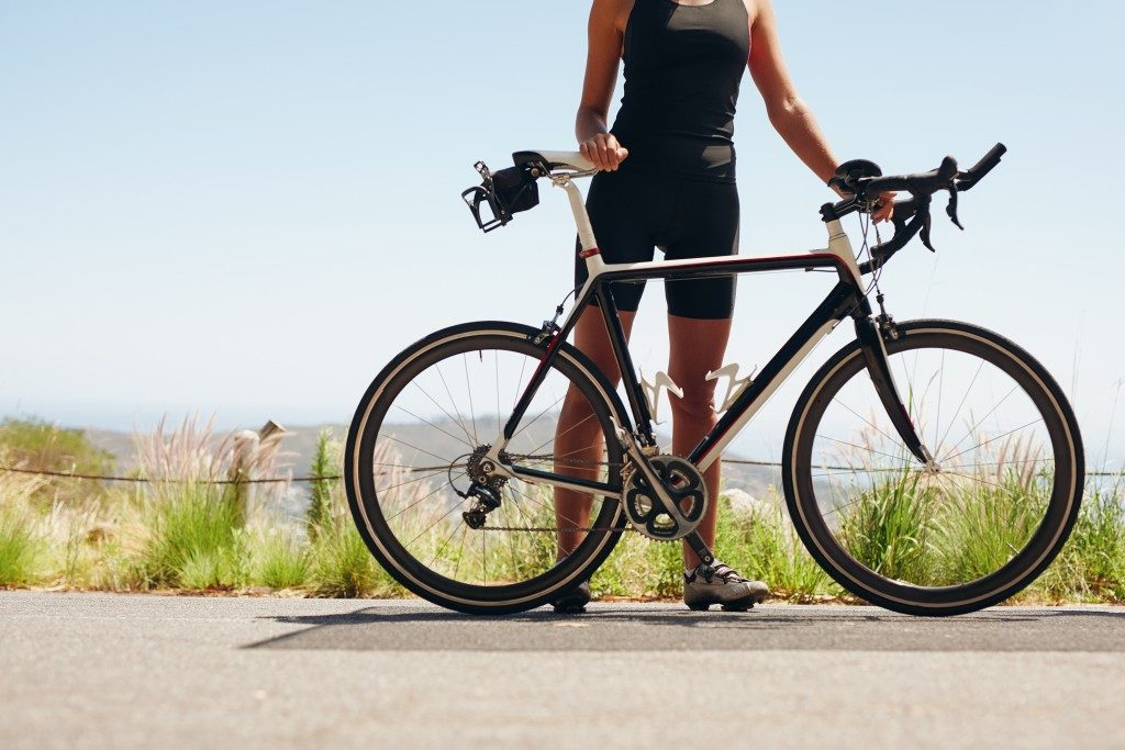 Low section shot of female athlete standing with her bicycle