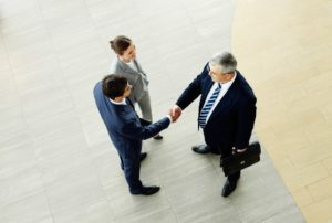 Employees wearing corporate attire shaking hands