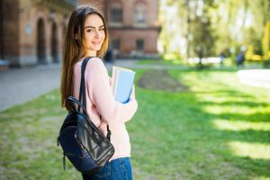 a girl in a university carrying a bag and a set of books
